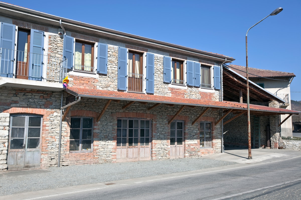 La facciata della casa in tipica pietra di langa con la tettoia parcheggio e subito dopo l'accesso alla vecchia segheria,attuale entrata dell'affittacamere
