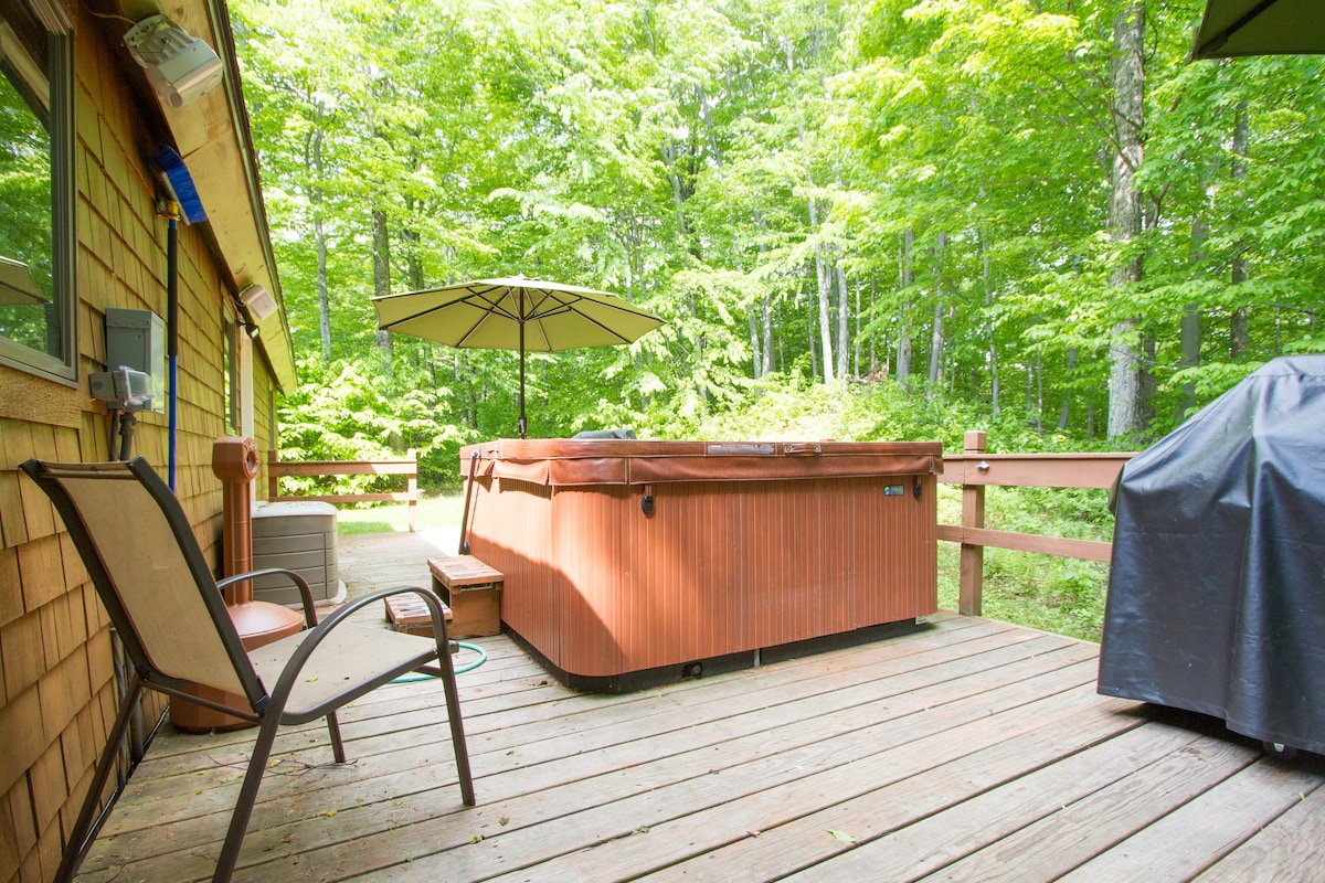 Back deck with hot tub, chairs, BBQ grill and umbrellas.