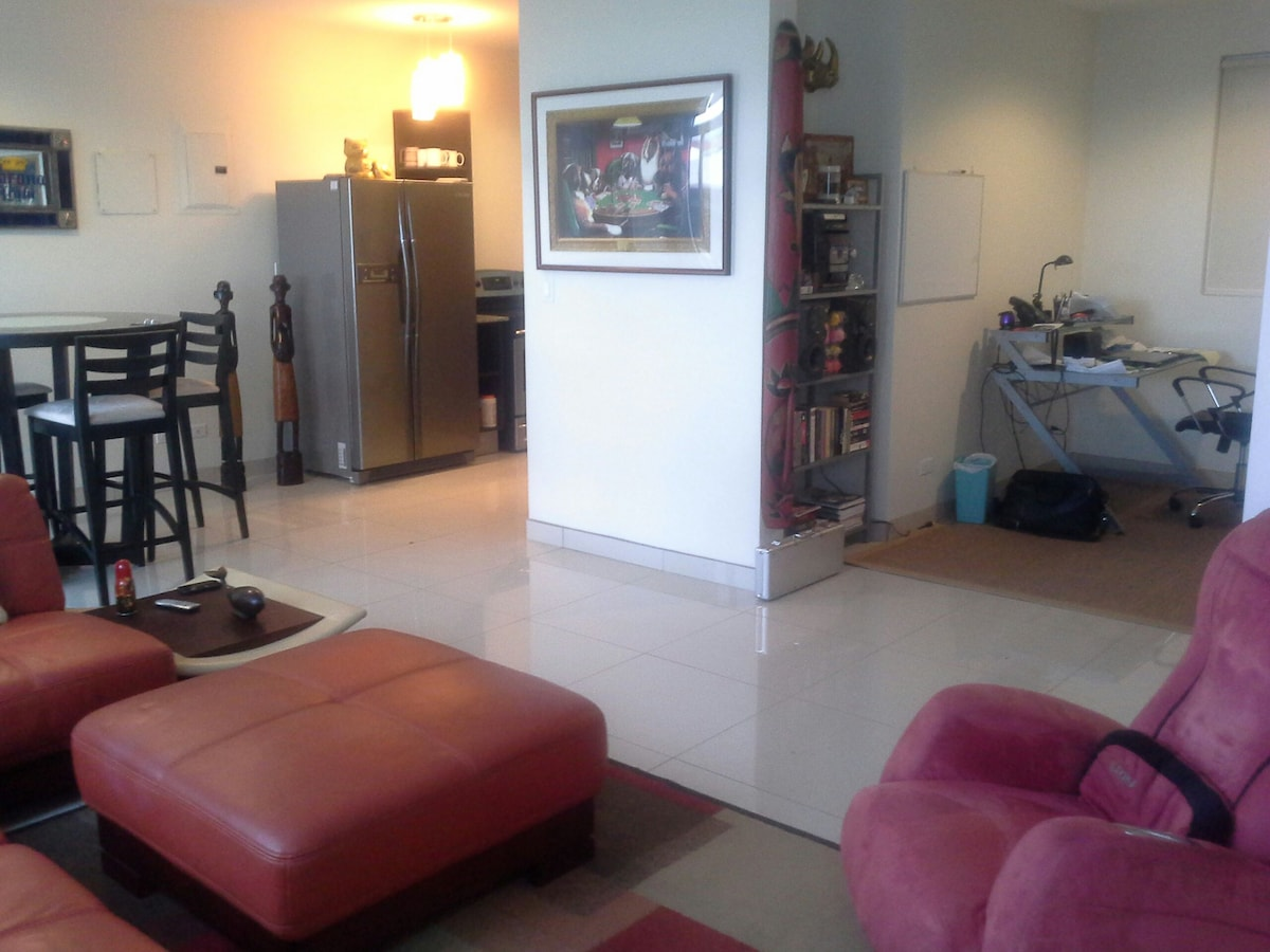 View from back of living room.  on left you see bar table set, in center is kitchen and on right you see the office area.