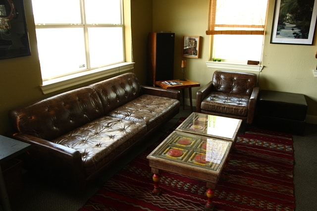 Living room has long comfy couches and beautiful table tables and rugs