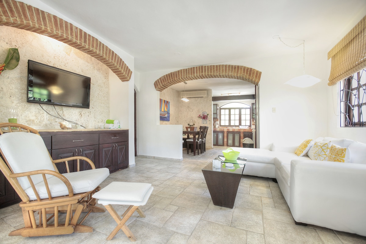 """Living room area with 42"""" plasma TV. Dining room and kitchen in the background."""