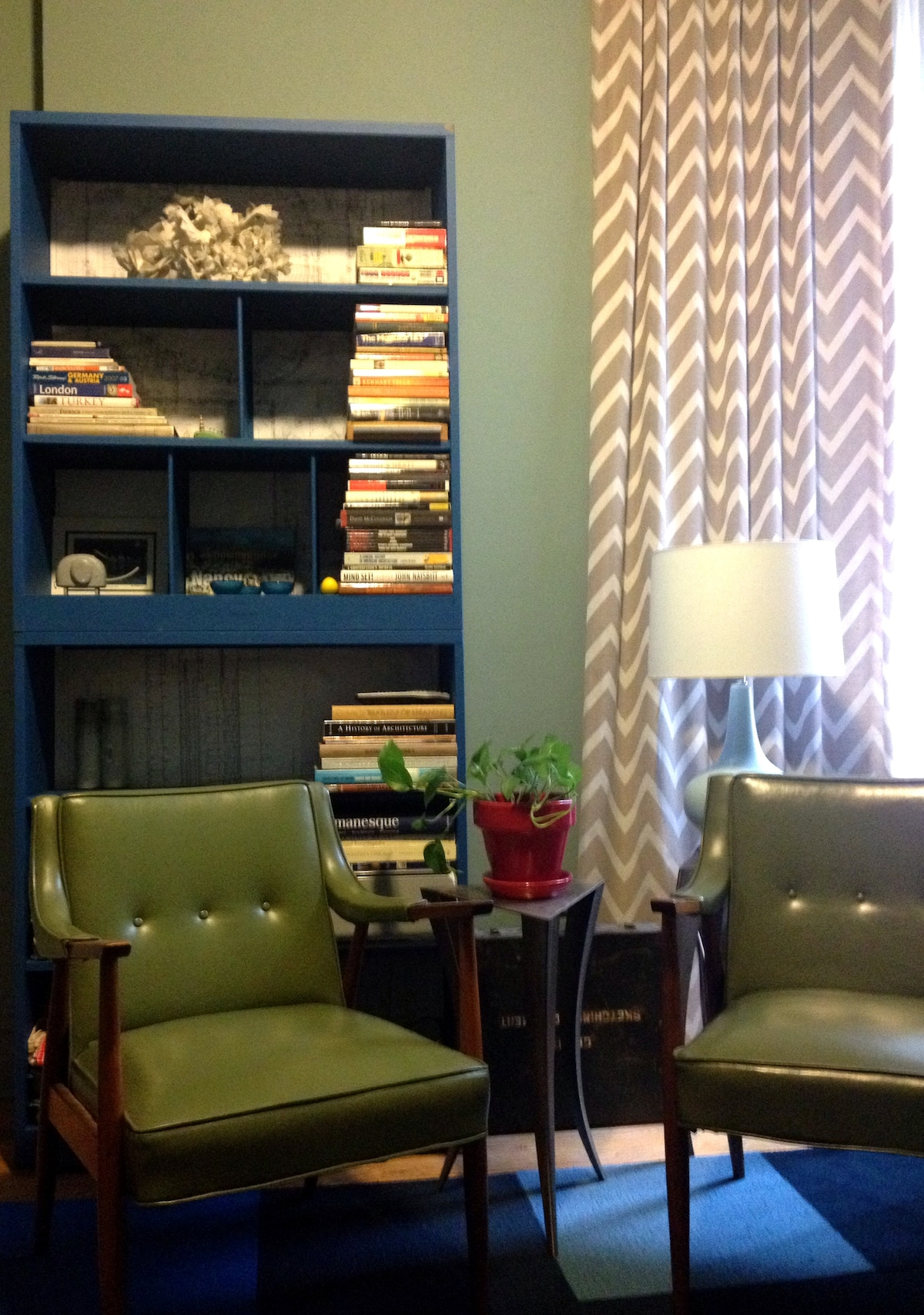 My eclectic living space. Mid-century modern armchairs with vintage school bookshelves makes the space super comfy.