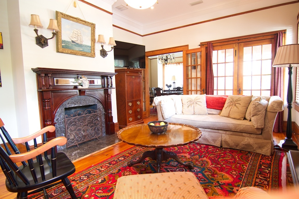 Living room with Perian rug, flat screen TV, gas fireplace and plenty of seating.
