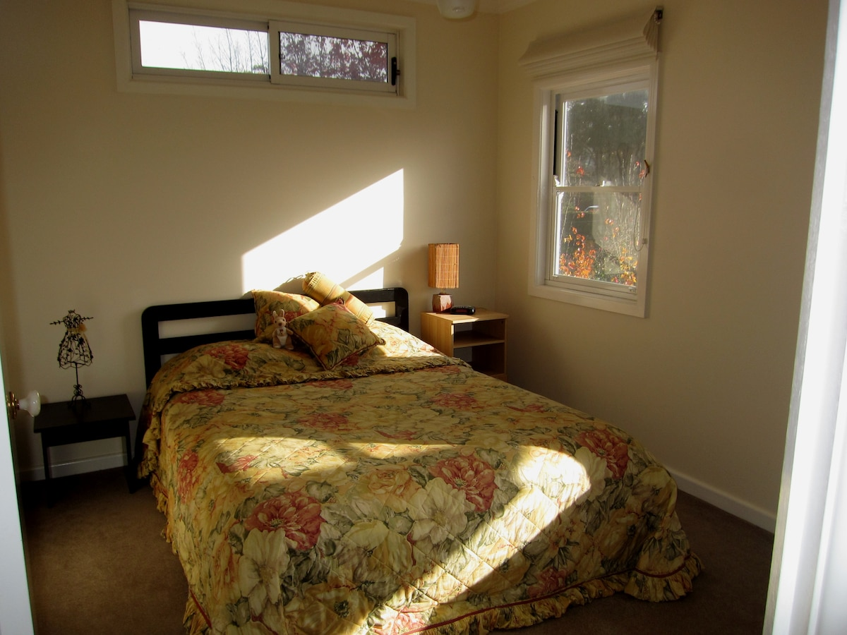 Sun filled room with Queen Bed and walk in robe.