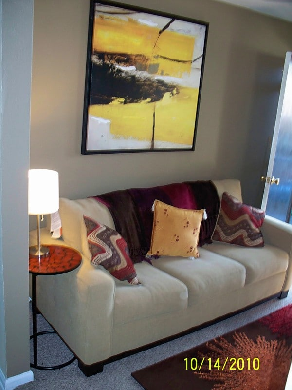 Comfy full size sofa in living room with bold wall art.