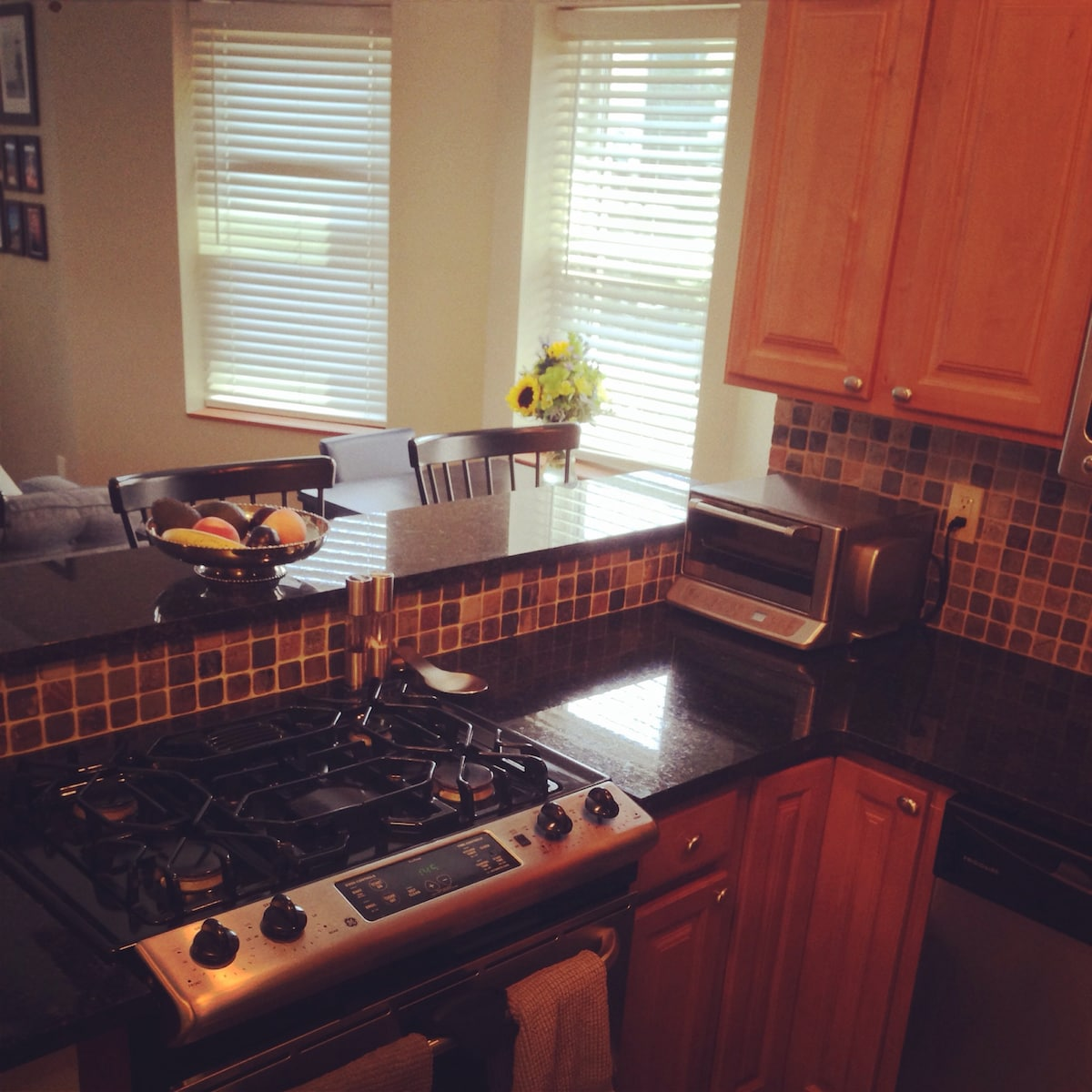 Modern kitchen with granite countertops and stainless steel appliances. Coffee maker available for use. Breakfast bar with 3 stools.