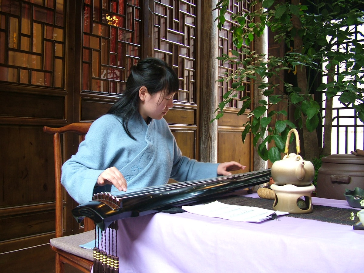 Essie is playing  Guqin, a seven-stringed plucked instrument in some ways similar to the zither