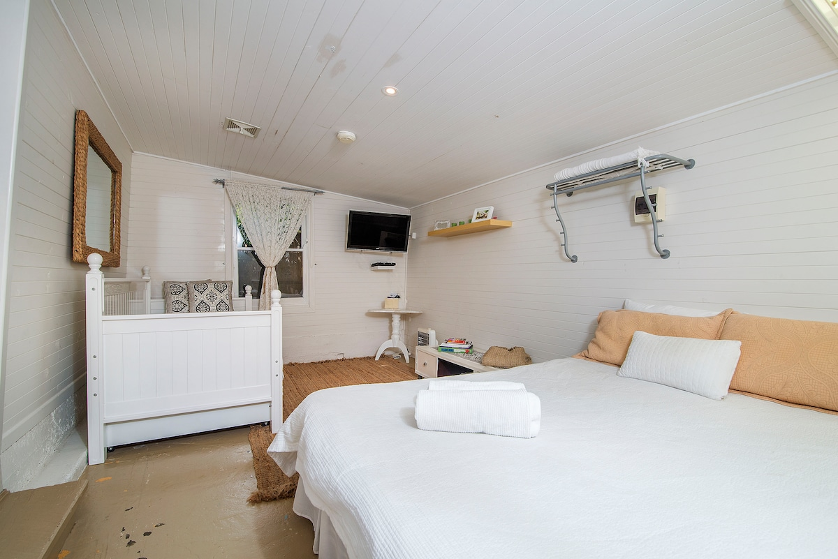The self contained Studio, Queen bed plus 2 Singles. Studio located behind the House.