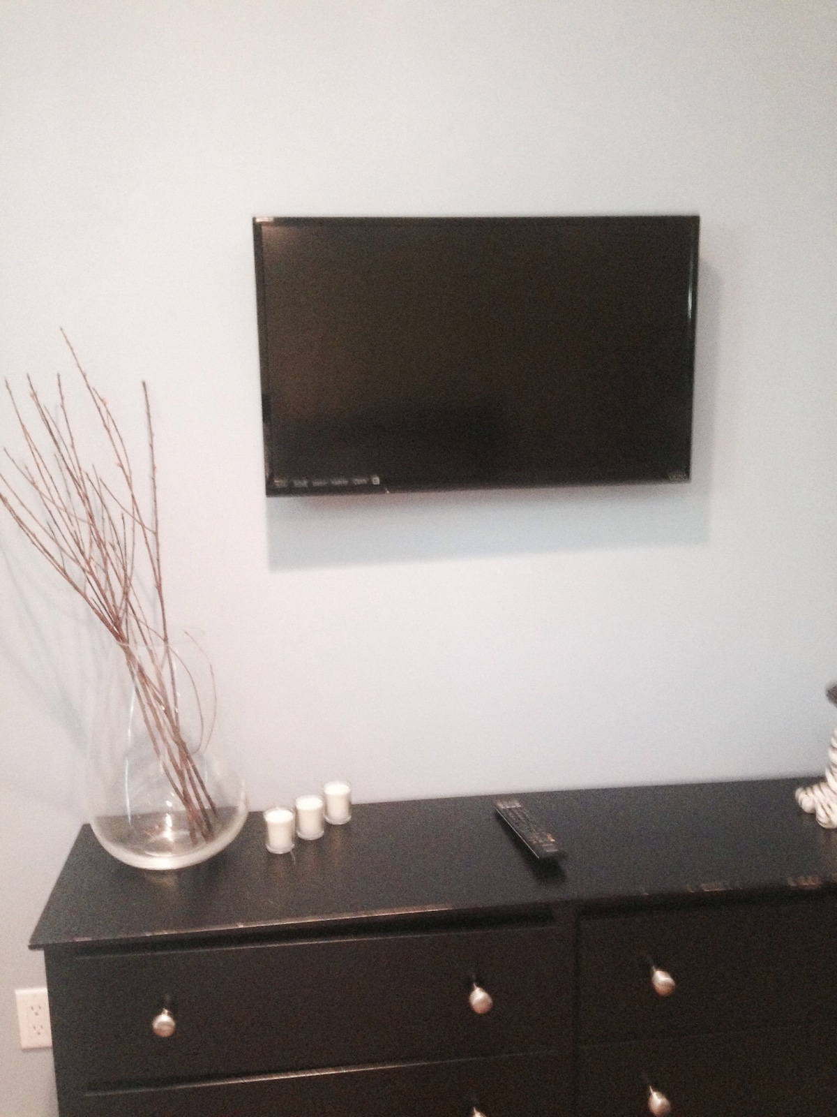Cable HDTV, futon, a large dresser and wardrobe rack.