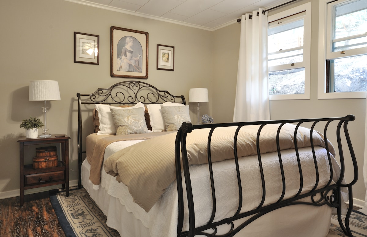 Luxurious bedroom with queen bed, dresser and large closet.