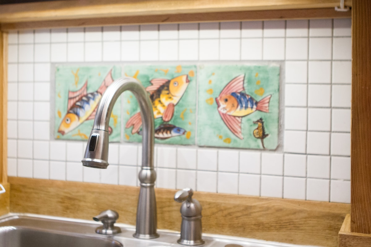 The kitchen sink is decorated with hand made tiles generously donated from the estate of Norma Morrison.