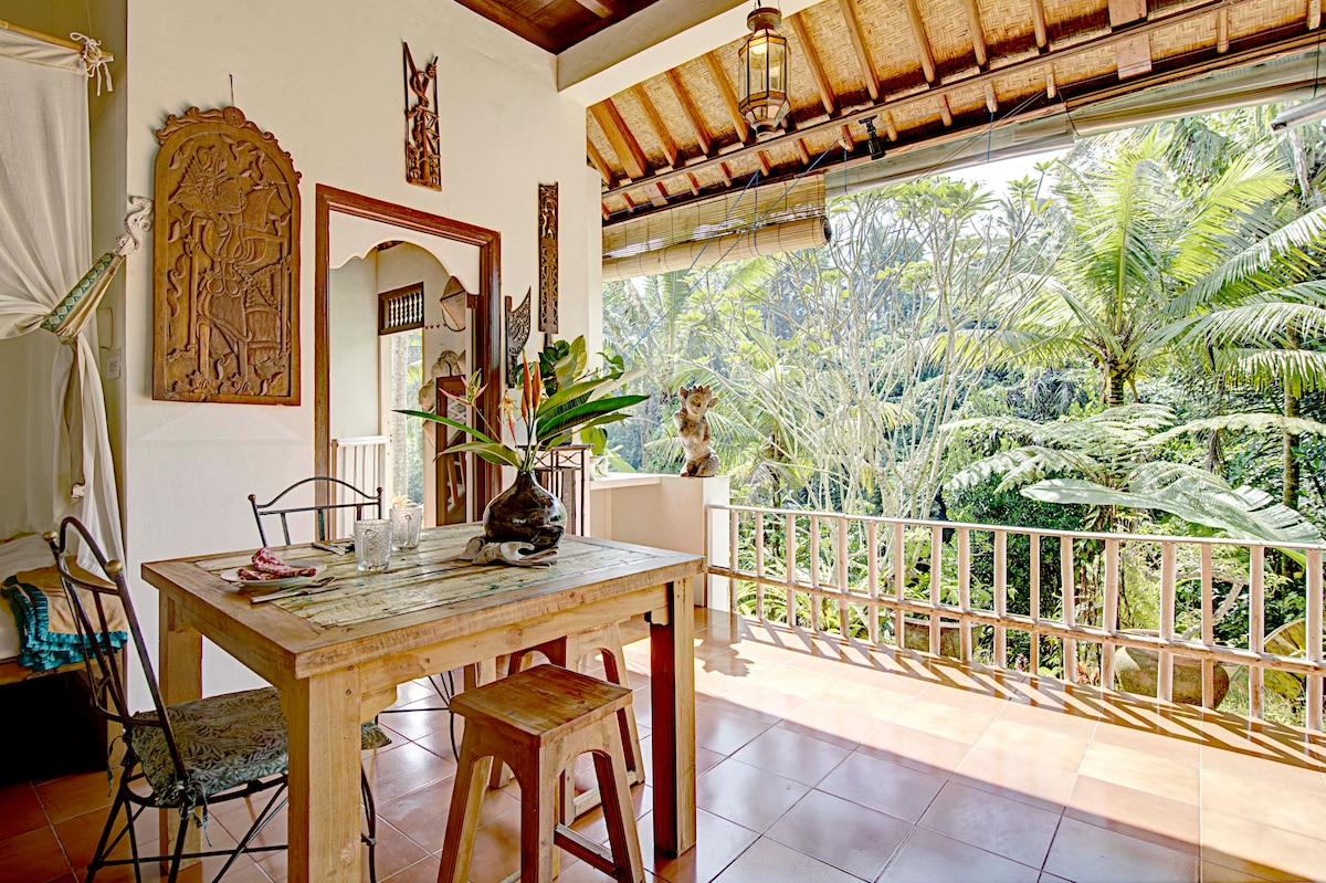 Dining area overlooking the jungle. Carved wood panel of Prince Arjuna ( a character in the epic MahaBarata)  and Scuptures by Papuan tribe. White washed Bamboo railing for safety