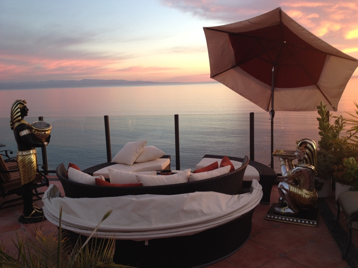 Queen bed on rooftop deck, sunset