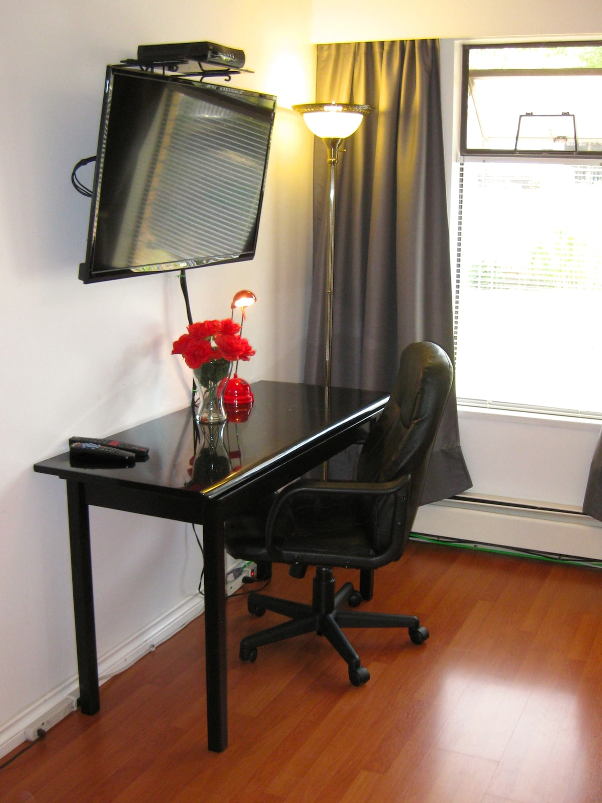 Ample work space on the black, marble desk/table with a comfy office  chair.