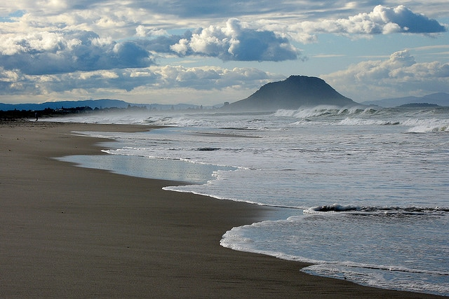 The Pacific Ocean sweeps up the beach with Mt Manganui in the background.