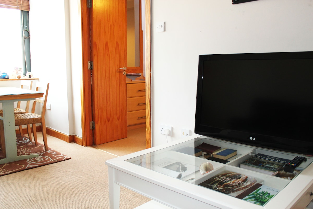 Living room with 37in flat screen TV, which has cable. There is also free high speed wifi throughout the apartment.