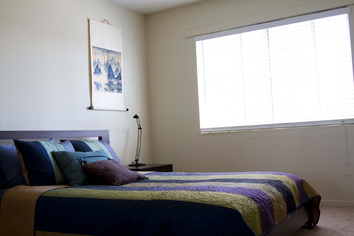 The master bedroom has a queen-sized bed and receives lots of sunshine.