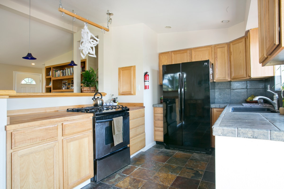 Kitchen with stone floors, gas range, digital oven, dishwasher, wood and stone counters.