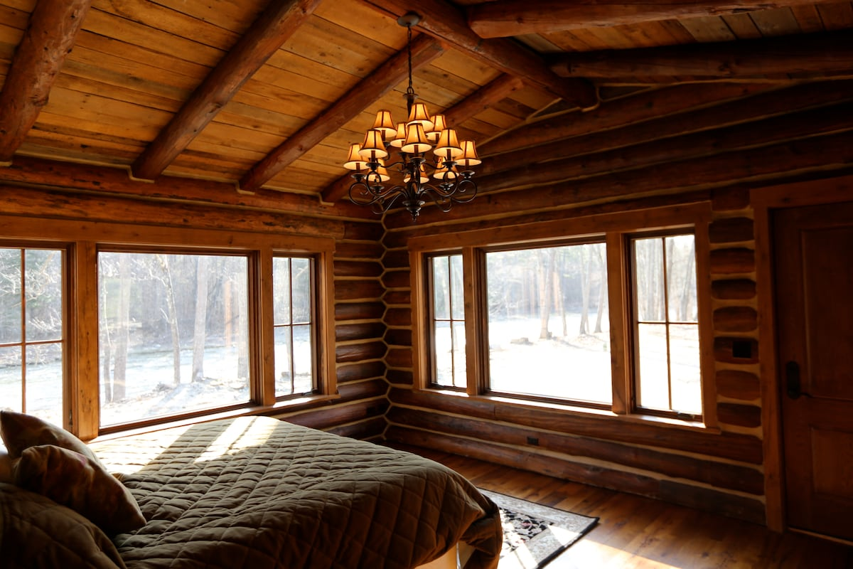 Log cabin room with king bed and two person soaking tub