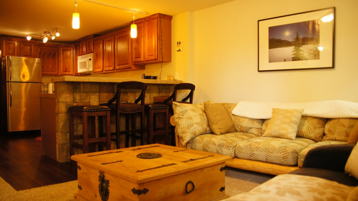 Lounge seating area leading into the kitchen with bar seating for four people.