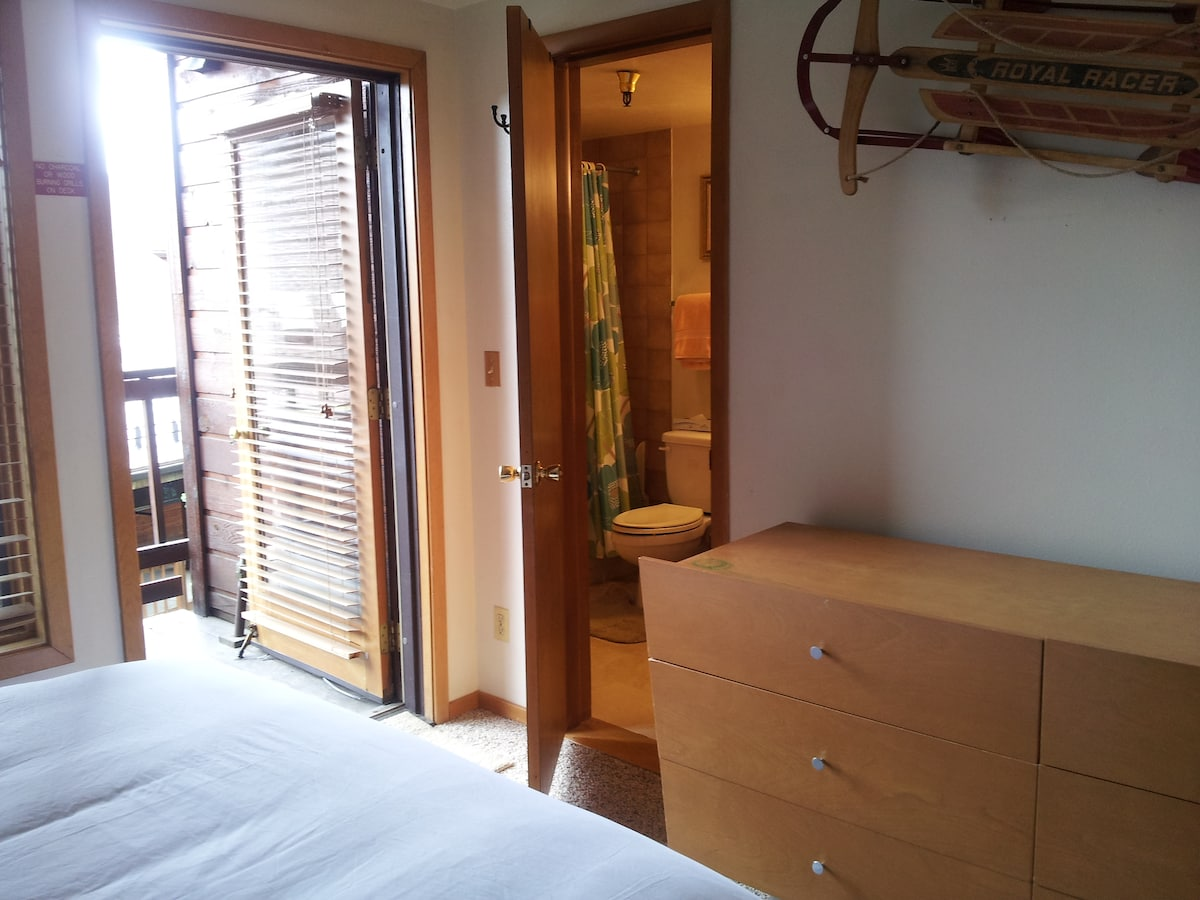 The bedroom area provides access to the deck and also has a second door into the bathroom
