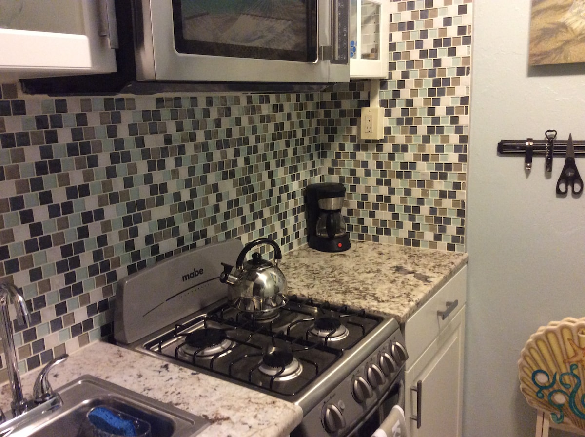 The full kitchen features granite tops and stainless appliances.