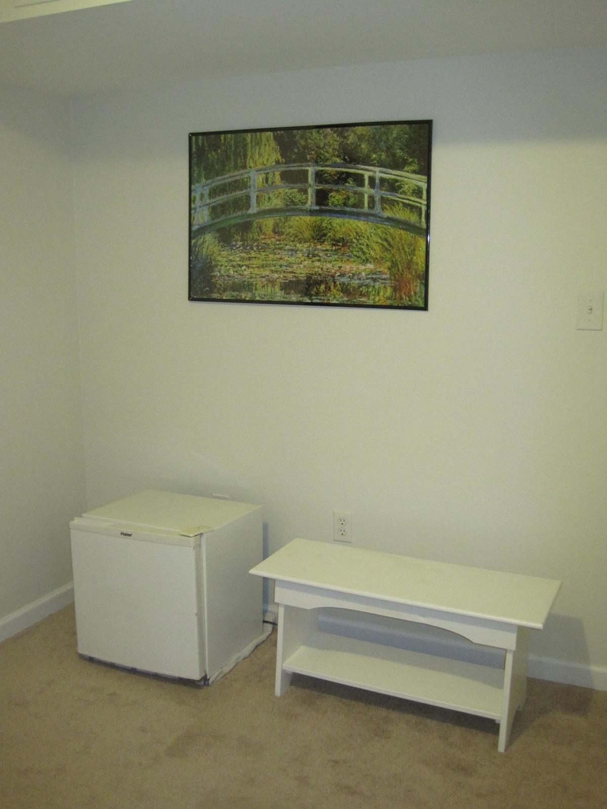 Mini fridge and bench in bedroom.