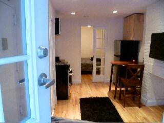kitchen and bedroom w/ Queen bed behind door