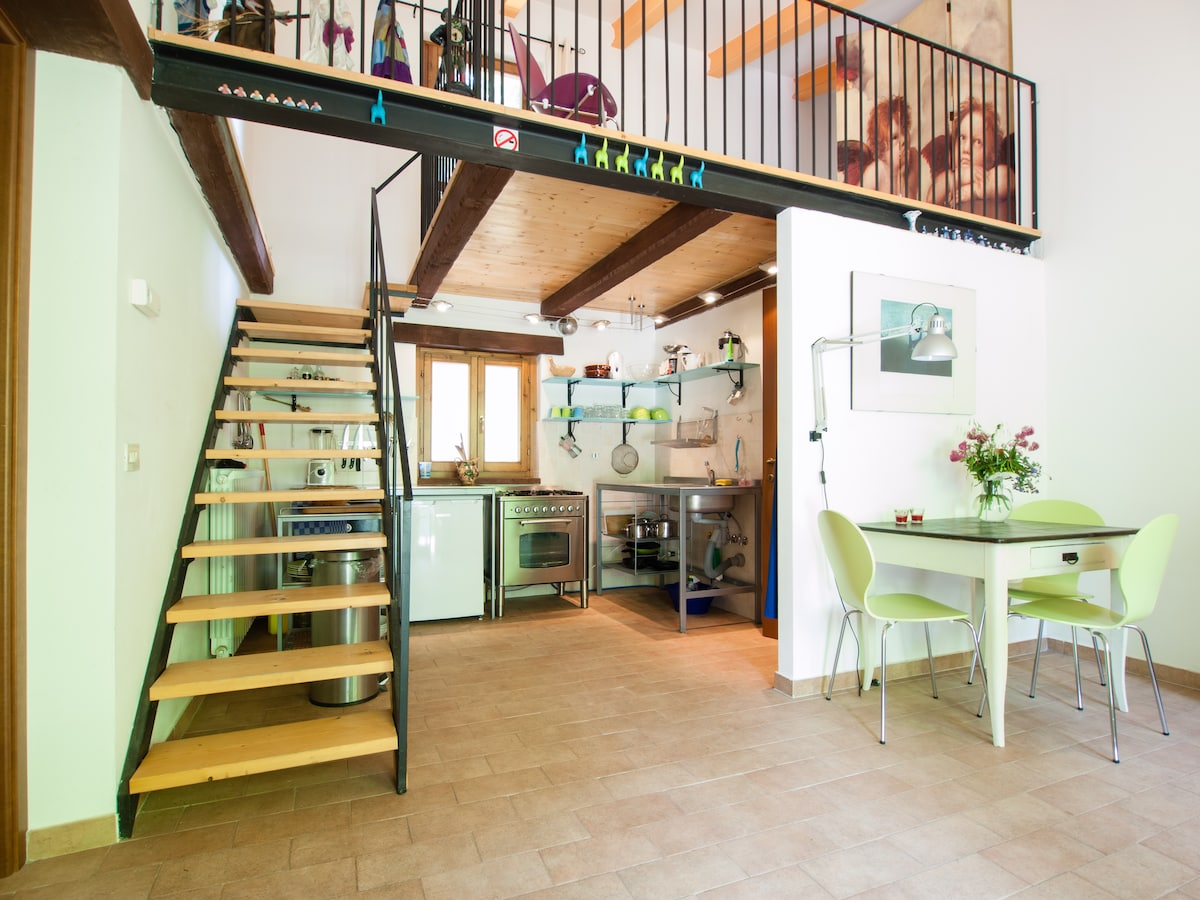 cosy livingroom with functional kitchen and stairs to one of the bedrooms in 'vista sul mare'