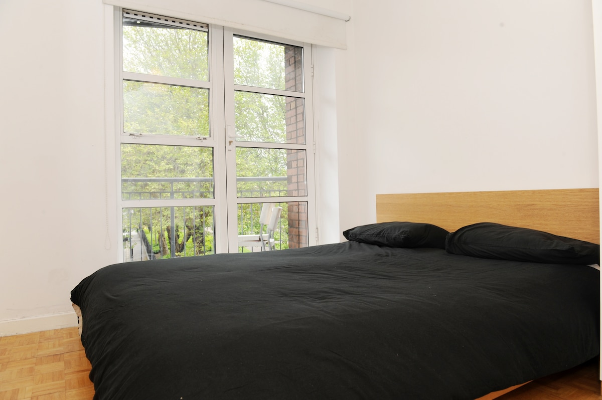 Bedroom.  Large double bed.  Corner wardrobe with ample storage space.  Very bright room.