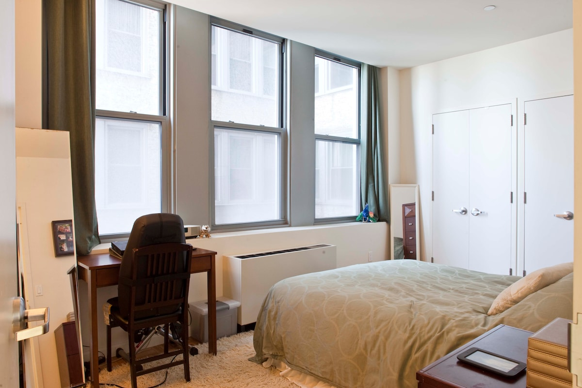 Bedroom features central air, heat, and tall windows with plenty of natural light