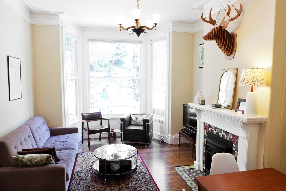 spacious but cozy living space with tons of light on tree lined Noe street