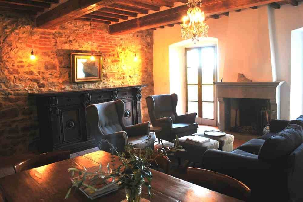 Living room with traditional fireplace with doors to terrace. Soggiorno con camino tradizionale con porte a terrazza.