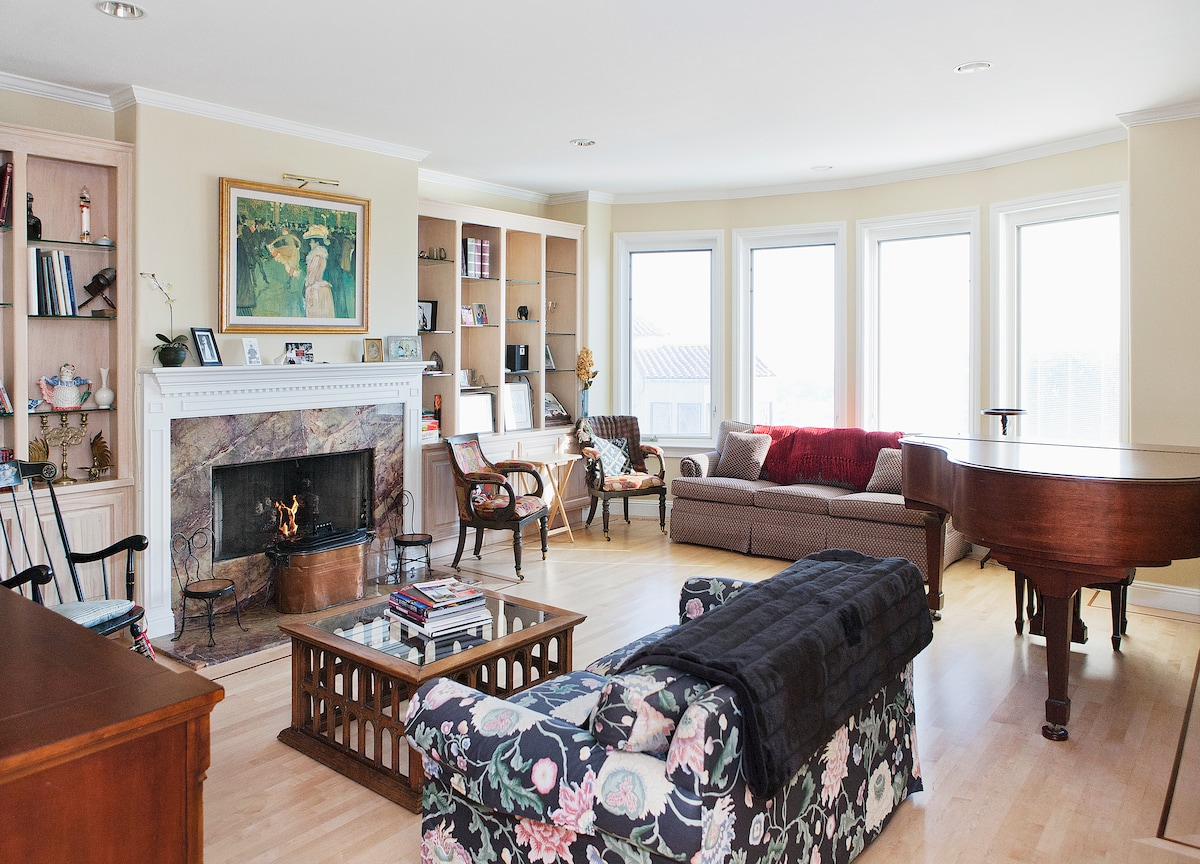 The living room has gas fireplace, recessed bookshelves, television and a Steinway grand piano.