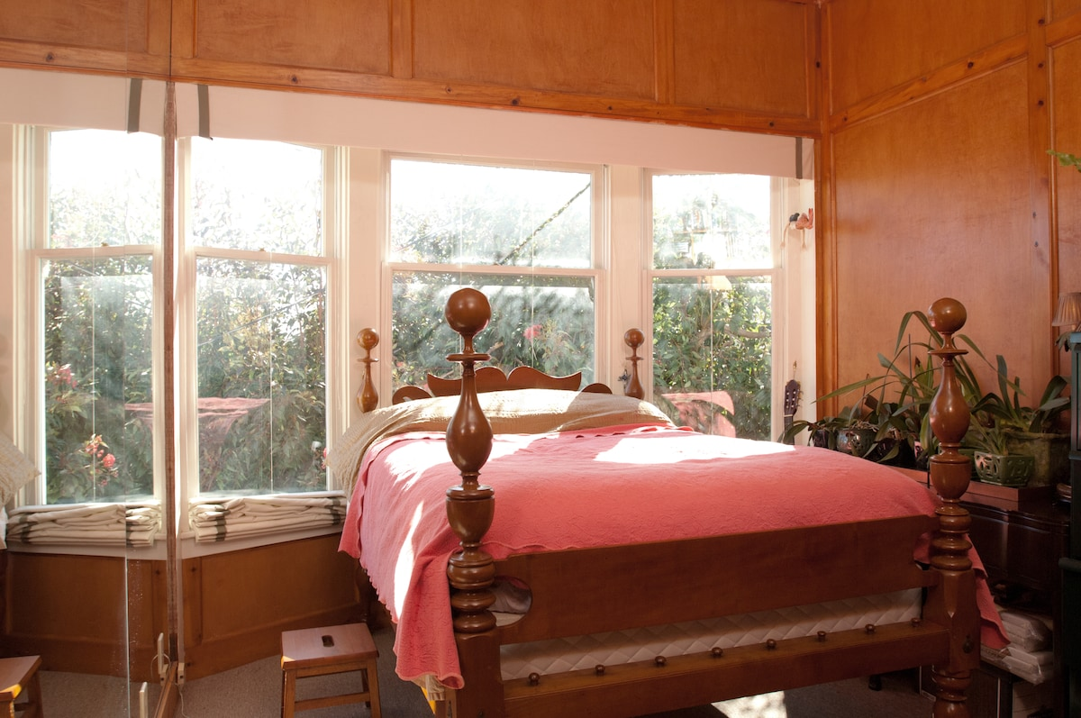 Antique double bed, lots of morning light, and roman shades which pull up to cover the windows.