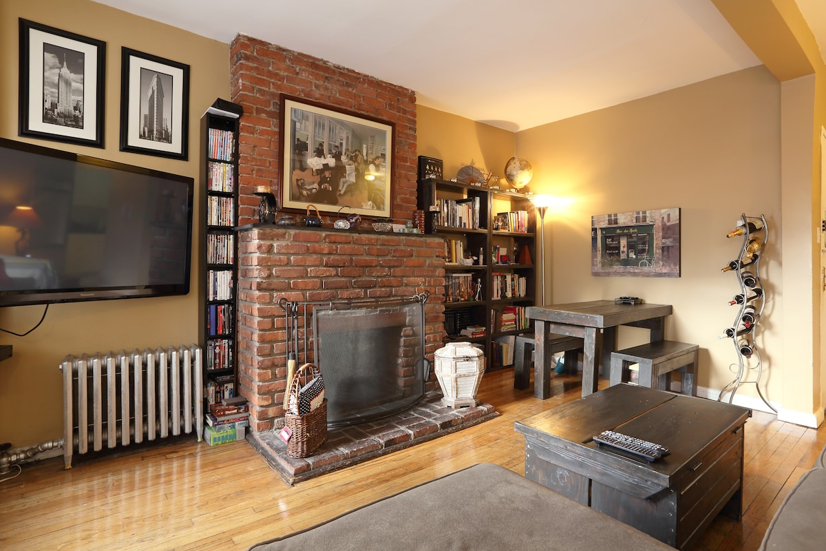 Living room features a brick fireplace, a dining table for five and a 50-inch plasma TV.