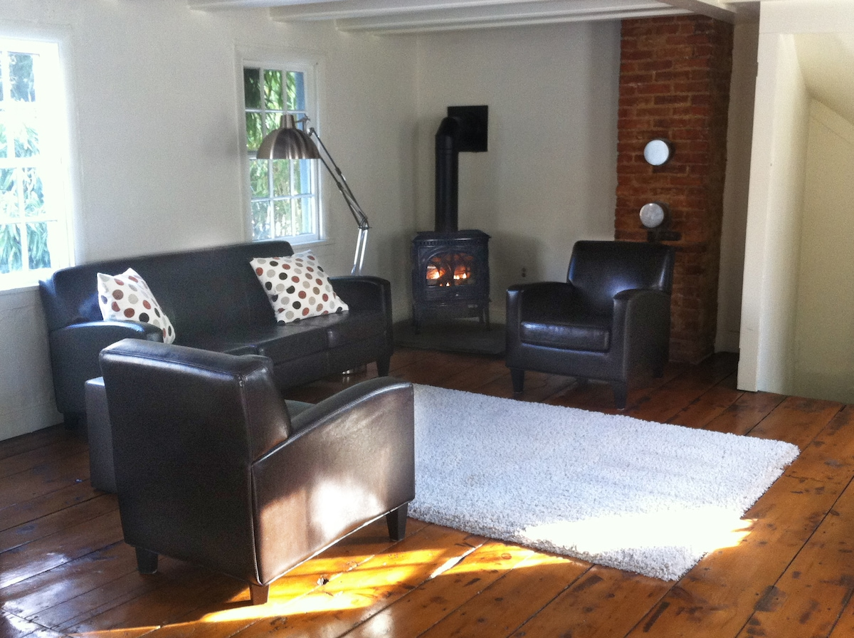 The living room with the quaint cast-iron stove lit on a chilly day.