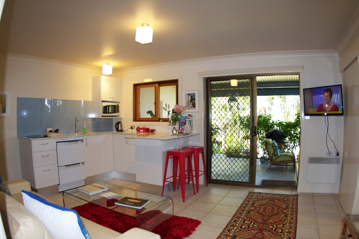 Look out from the kitchen and sitting area onto a lovely tropical garden.