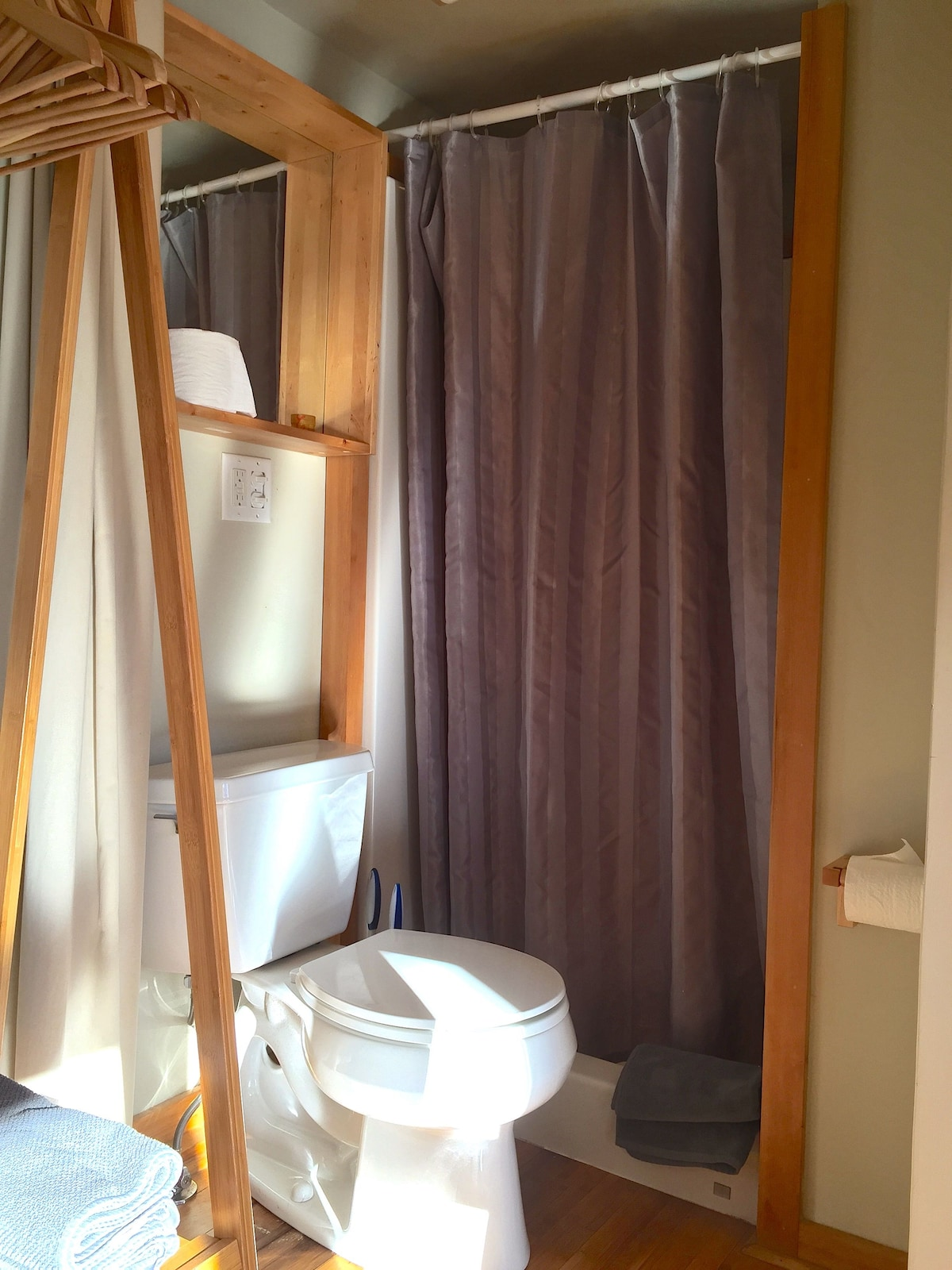 A compact bathroom is separated by a curtain. Please plan to bring your own toiletries. Fresh towels are provided.