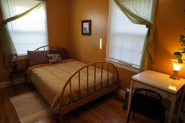 Sunny guest room with double bed and desk.