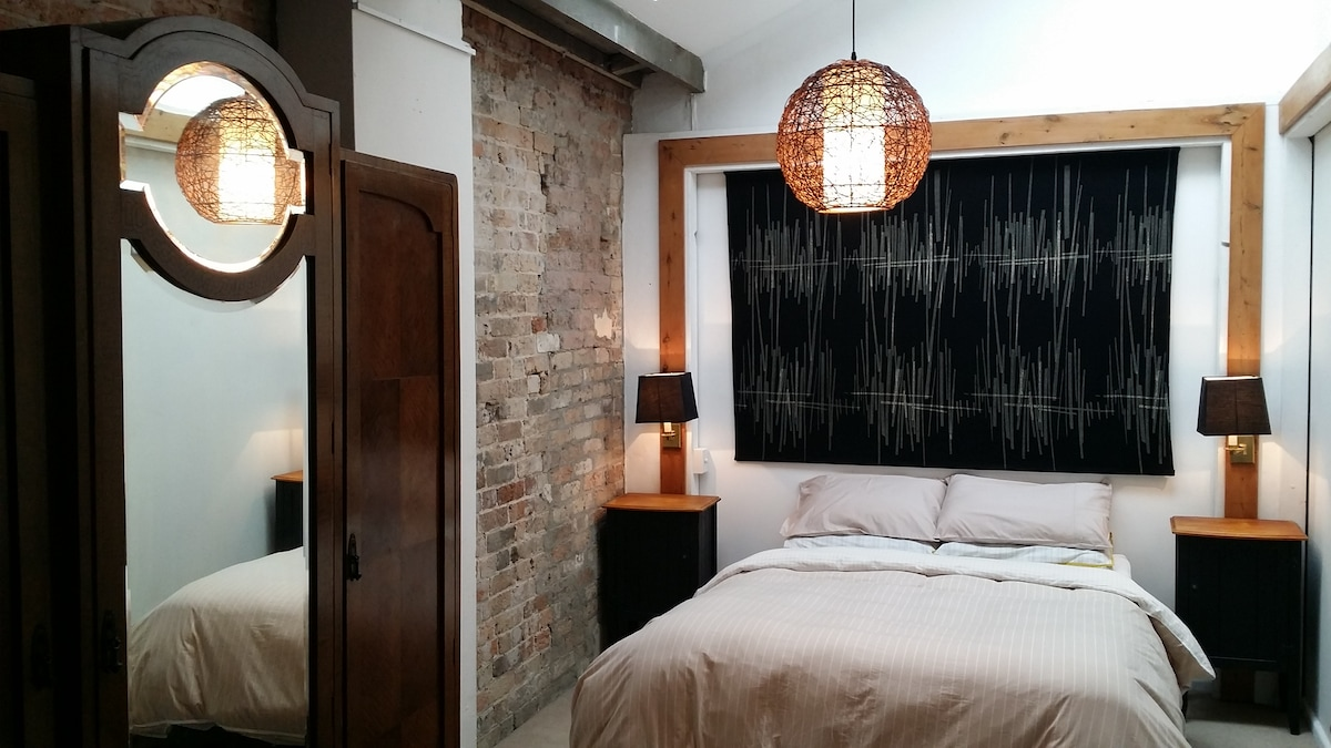 Bedroom 1 with exposed brick walls, warm antique furnishings, ample natural sunlight and plenty of comfortable dreamtime.