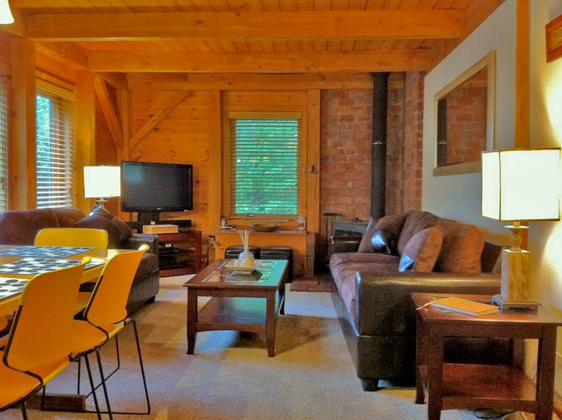 Living room with flat screen TV, WiFi, Roku media player, cable, BluRay, stereo and wood burning stove.