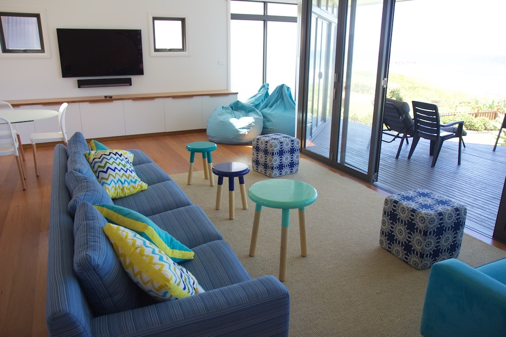 Open living, bi-fold doors leading to timber deck with beach views.