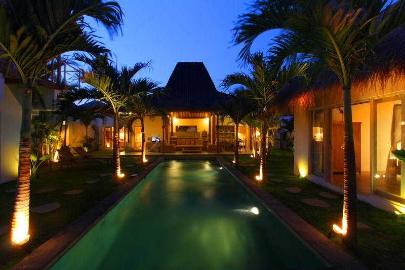 Property view by night. From left to right, one bedroom in a small house on the left of the pool, one bedroom, living room and one other bedroom in the main house, and one bedroom  in a small house on the right on the pool.