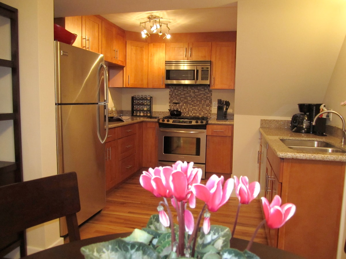 Well-equipped gourmet kitchen with granite countertop, gas stove and eating bar.