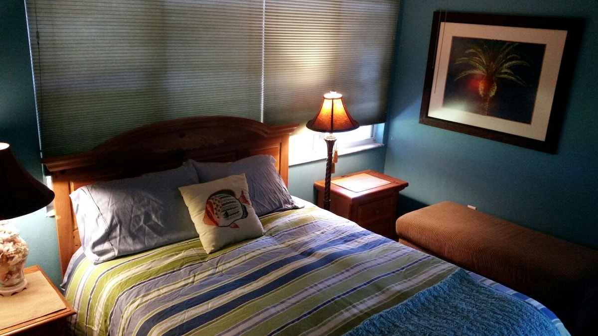 Queen size bed with feather duvet. Night stands with lamps on each side of the bed for reading.