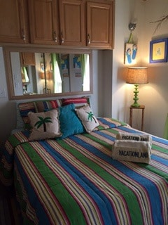 Queen bed with lights and storage above bed