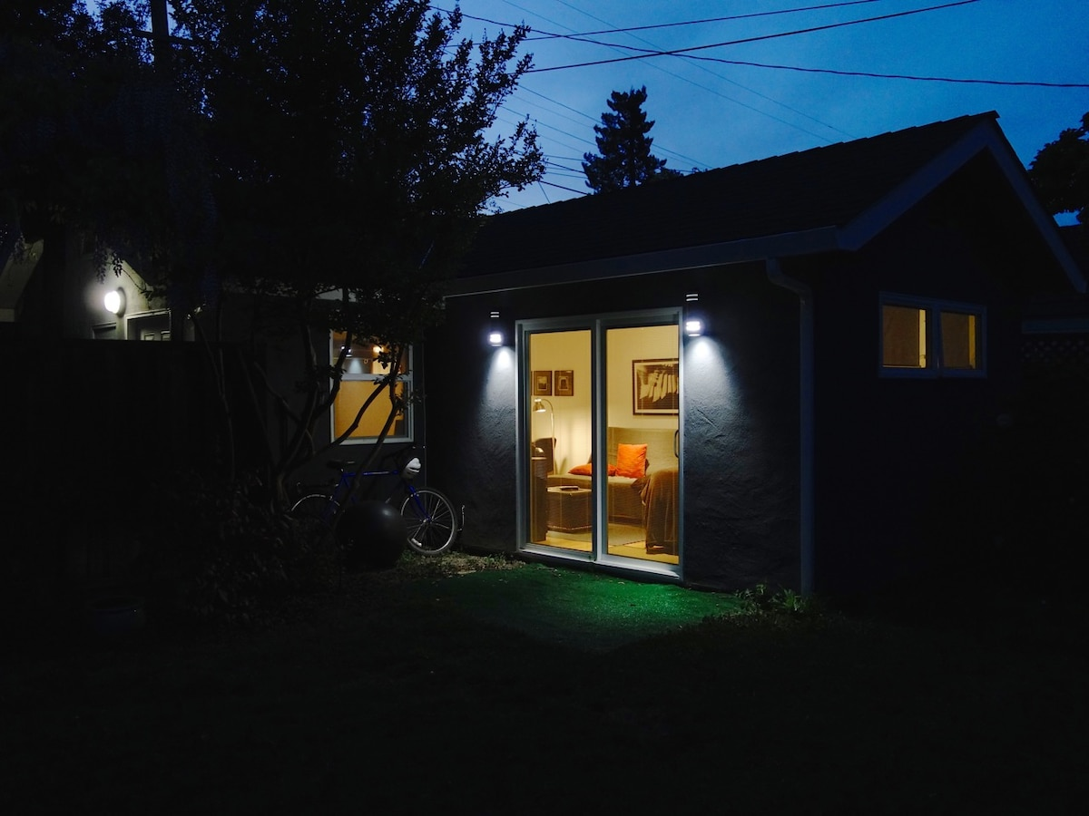 Exterior from the side yard at night.  Built in shades can be shut for privacy.