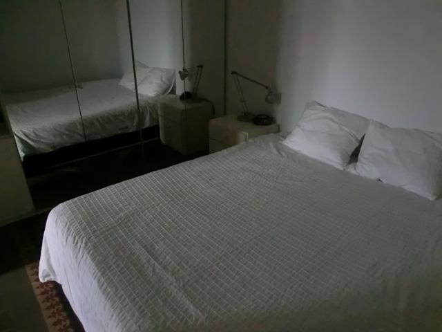 Habitación con cama de matrimonio y gran armario con espejo.