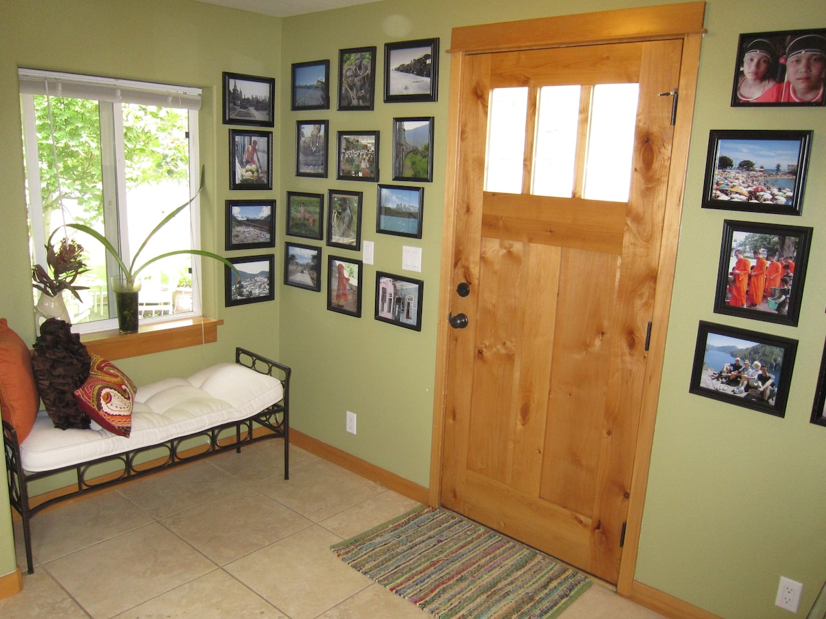 Bright open entry hall with photos from around the world. Bench can be placed in living for extra seating.